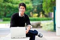 A shot of an asian student studying on his laptop