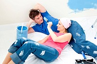 Joyful couple lying on the floor after painting a room in their new house with blue color