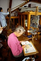 Elderly Woman Painting In A Modelling Art Class Studio