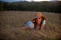 Pretty teen girl, straw hat, lying in field.