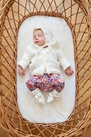 Newborn girl sleeping in a wicker bassinet