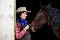Cowgirl petting a horse, Saskatchewan, Canada, North America