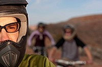 Closeup and cropped view of a male mountain biker in a helmet and protective eyewear. In the background are two other bikers. Horizontal shot.