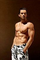 Sexy fitness model in swim trunks with copy space