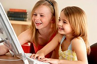 2 Young Girls Using Computer At Home