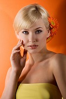 young beauty blond girl with yellow top and hair style with gerbera on orange background looking in camera