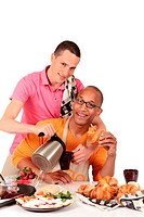 Attractive young mixed ethnicity gay, homosexual couple, Caucasian and African American in kitchen, preparing breakfast. Studio, white background.