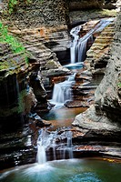 Waterfall in woods with rocks and stream in Watkins Glen state park in New York State