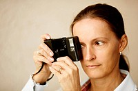 Woman with old film camera ,focus point on eye ,natural light
