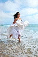 Happy Bride Running Through the Ocean in Wedding Dress. Image has slight motion blur.