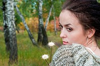 beauty girl with two flowers on meadow on the birch trees background