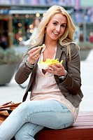 Pretty young girl in the city eating fries with mayonaise