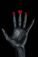 silver man´s hand with a heart symbol on his fingers