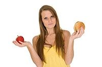 Caucasian woman holding an apple and hambuger trying to decide whichone to eat