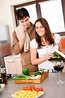 Smiling couple in modern kitchen cook together with cookbook