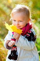Portrait of adorable toddler girl with yellow leave