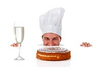 Attractive young caucasian chef man being tempted, peeping above table. Studio shot. White background.
