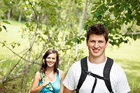 Young backpacking couple smile at the camera while hiking in the countryside.