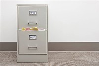 Shot of a filing cabinet with labels reading hired and fired. The ´fired´ drawer is very full. Horizontally framed shot. Copy space on right.