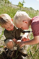 Two young brothers crouch down to inspect objects on the ground using a magnifying glass.