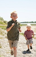 Two young boys run across the dirt towards the camera on a sunny day.