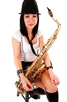 A young Asian woman sitting in the studio, playing the saxophone inshorts with suspender and a hat on her black hair, for white background.