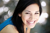 Portrait of a young woman smiling at the camera outdoors.
