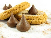 Peanut butter cookies with chocolate kisses on a plate with cinnamon.