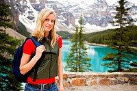 A portrait of a woman hiking on a mountain path near a lake