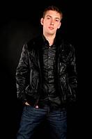Handsome guy in black jacket over black background.