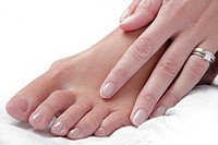 Nice photo of a womans foot and hand with a white background