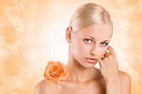 beauty portrait af sweet and nice blond girl with an orange rose on her shoulder looking in camera