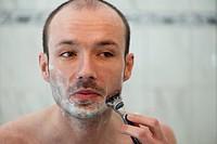 Spiegelbild eines jungen Mannes bei der Rasur