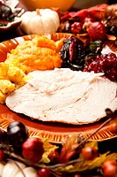 Thanksgiving meal of sliced turkey breast, Swiss chard, mashed sweet potato, stuffing and cranberry sauce