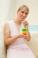 Junge blonde Frau trinkt einen bunten Cocktail