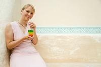 Blonde Frau trinkt lachend einen Cocktail auf einer Steinbank sitzend