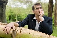 Junger Mann lehnt im Park an einem Baumstamm und schaut nachdenklich in die Ferne