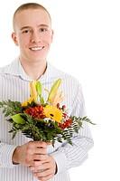 Junger Mann hält lachend einen Blumenstrauß in den Händen