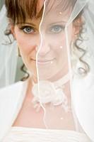 Portrait einer jungen Braut mit weißem Schleier vor dem Gesicht