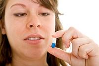 Junge brünette Frau schaut eine weiß_blaue Kapsel zwischen ihren Fingern an