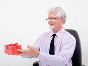 senior businessman holding a gift over white