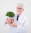 senior scientist holding small poted tree