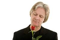 Mann schaut eine rote Rose an