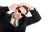 Mann im Anzug und mit Sonnenbrille kämmt sich die Haare