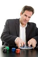 Mann am Tisch mit Pokerchips mischt einen Kartenstapel