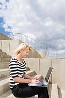 Junge Frau arbeitet auf einer Außentreppe sitzend an ihrem Laptop