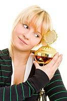 Junge Frau in Sportkleidung umarmt einen Pokal