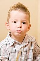 Vierjähriger Junge kaut mit dicken Wangen beim Frühstücken