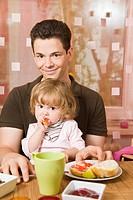 Glücklicher Vater sitzt mit seiner kleinen Tochter am Frühstückstisch