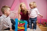 Blonde Frau sitzt im Kinderzimmer und spielt mit einem Jungen und einem Mädchen